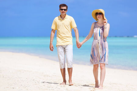 young couple at the beach, holding hands together photo