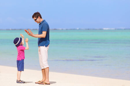 fun day: little boy giving his father high five at the beach, spending fun day together during summer vacation Stock Photo