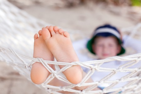 closeup of little boys feet, who is relaxing in the hammock during his summer vacation photo