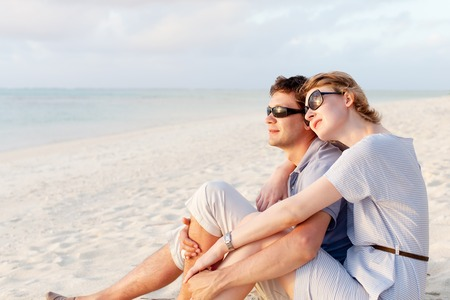 young couple sitting at the beach, romantic moment during summer vacation photo
