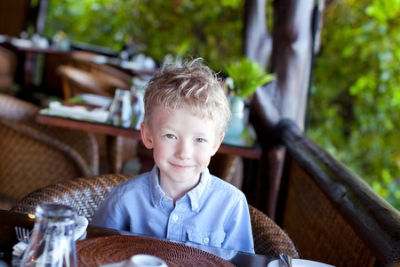 little cute boy waiting for his breakfast at the hotel photo