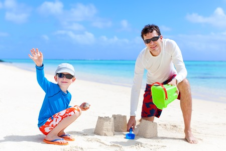 happy family of two building sandcastle together at the beach photo