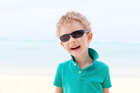 motu: smiling little boy having fun at the beach during summer vacation