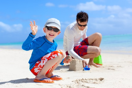 cheerful family building sand castle at the beach photo