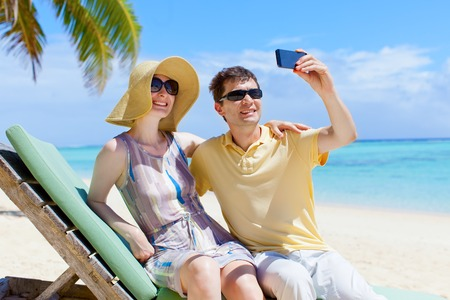 happy couple taking picture during tropical vacation at the beach photo