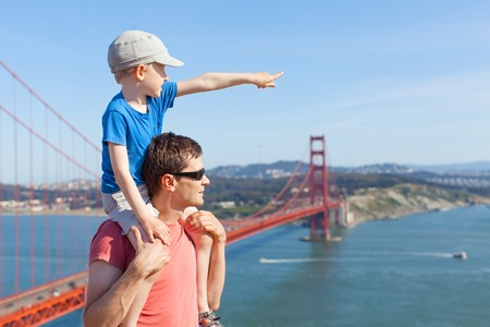 little son sitting at his father shoulders and enjoying together the view of golden gate bridge in san francisco, california photo