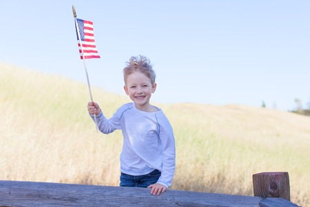 cute little boy holding american flag and celebrating independence day photo
