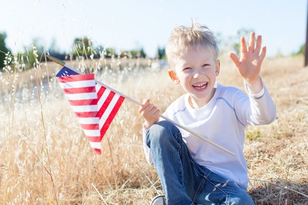 cute little boy holding american flag and celebrating independence day