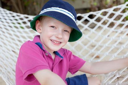 motu: cute smiling boy enjoying tropical vacation in the hammock Stock Photo