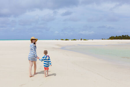 motu: young mother and her son walking at the perfect tropical beach at aitutaki, cook islands