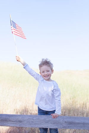 little boy holding american flag and celebrating 4th of July photo