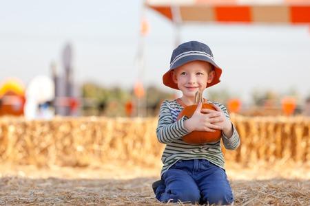 fall festival: little boy at pumpkin patch holding pumpkin Stock Photo