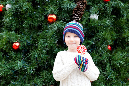 little cheerful boy holding candy and enjoying christmas time photo