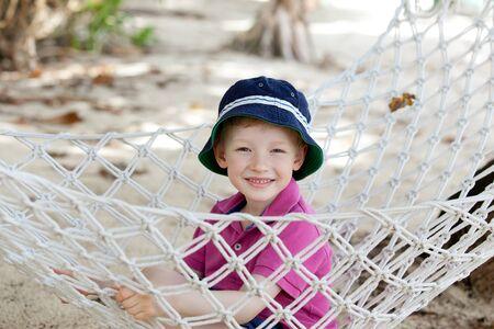 motu: happy smiling boy in the hammock at the beach