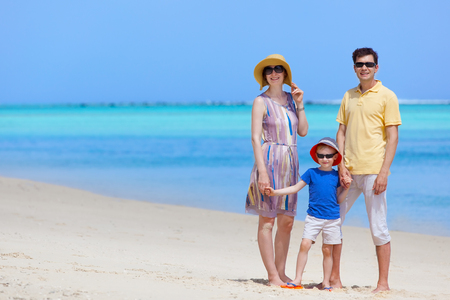 happy family of three at the tropical beach photo