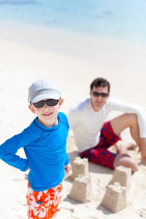 happy father and son building sand castle at the beach photo