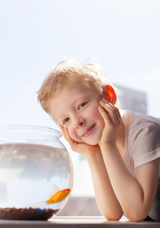 cute cheerful boy with goldfish photo