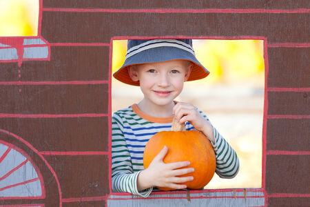 cheerful little boy at pumpkin patch, fall time photo