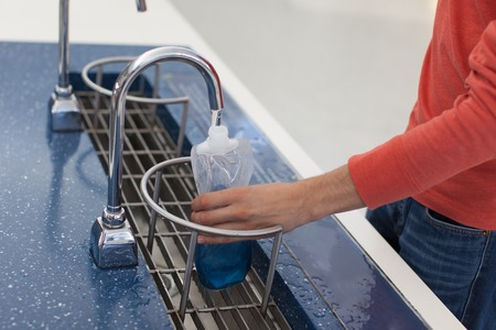 refilling: person refilling bottle with drinking water, save the planet concept Stock Photo