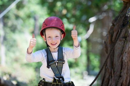 niño trepando: valiente niño que se divierte en el parque de aventura y dando los pulgares dobles para arriba Foto de archivo