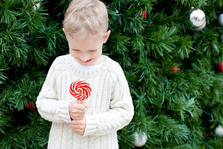 happy little boy holding candy at christmas time photo
