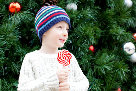 cute little boy with candy cane at christmas time photo
