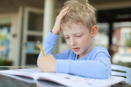 deberes: ni�o peque�o concentrado hacer la tarea