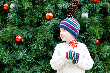 cute little boy holding candy by the christmas tree photo