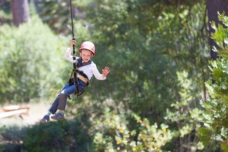 zip: brave little boy ziplining in adventure park