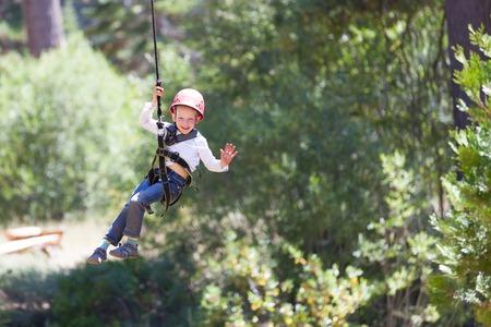 niño trepando: valiente niño tirolesa en el parque de aventura