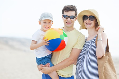 fun day: family of three enjoying fun day at the beach together playing with the beach ball Stock Photo