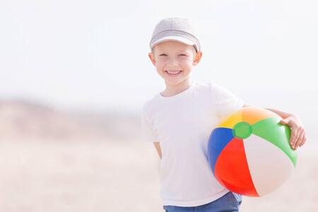 little boy with beach ball having fun photo