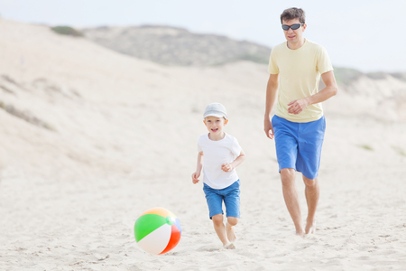 fun day: family of two enjoying fun day at the beach together playing with the beach ball