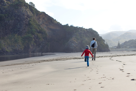 new zealand beach: family of two walking at piha beach near lion rock at north island in new zealand