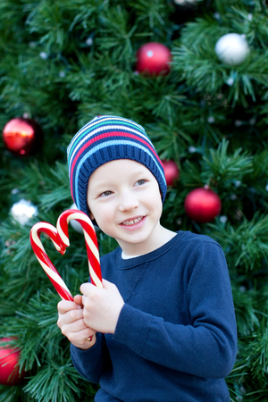 funny little boy playing with candy canes at christmas time photo