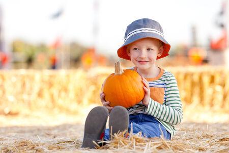 cute little boy holding pumpkin at pumpkin patch photo