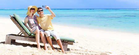 young couple taking picture of themselves at the perfect tropical beach photo