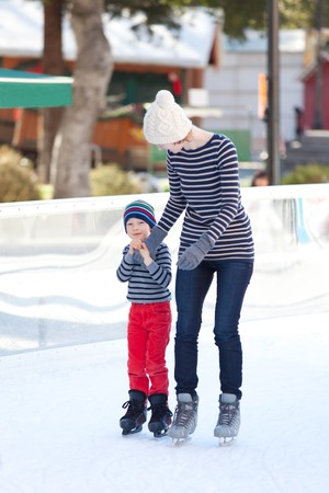 family of two having fun ice skating together at winter photo