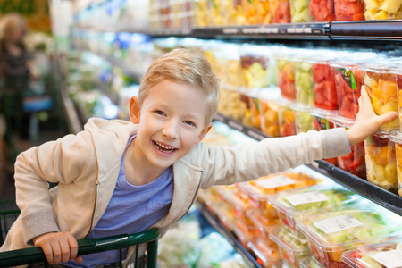 groceries: smiling positive boy grocery shopping at the supermarket sitting in the cart helping his mother Stock Photo