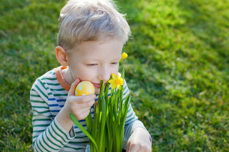 smiling positive boy with flowers and easter egg at spring time photo