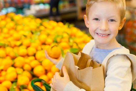 kid smile: smiling healthy boy holding reusable brown bag and buying mandarin oranges at grocery store