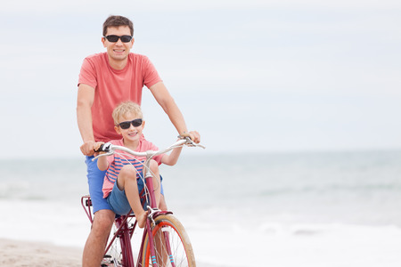 family of father and son enjoying riding bicycle together at the beach photo