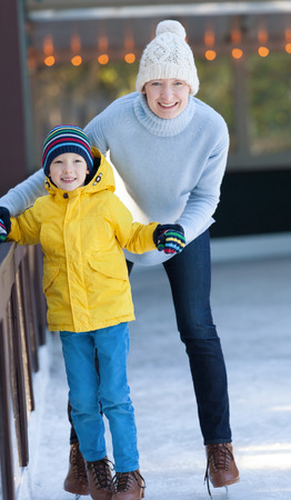young mother and her son ice skating together at outdoor skating rink at winter photo