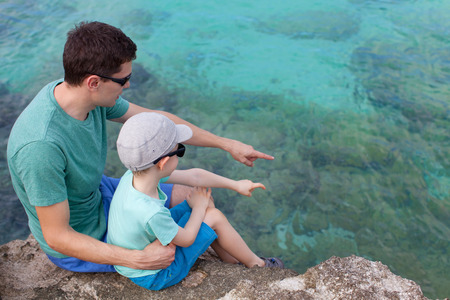 grand sons: young father and his son sitting at the rocky beach and exploring underwater life