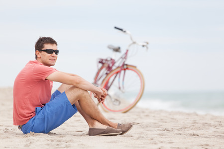 young man sitting at the beach and resting after bicycle ride photo