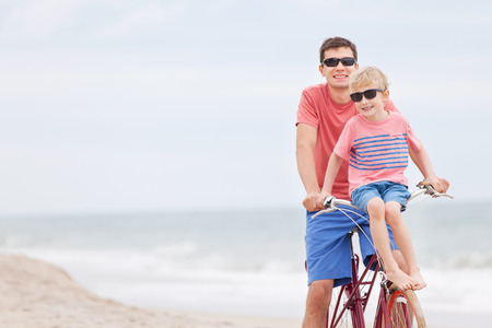 happy family of father and son enjoying their time together while biking at the beach photo