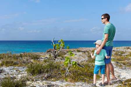 grand sons: family of two enjoying rocky beach at cayman islands