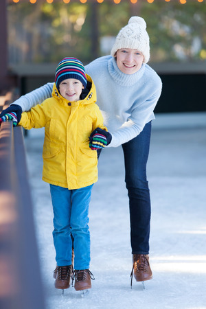 happy family of mother and her son enjoying ice skating together at winter at outdoor skating rink photo