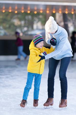patinaje sobre hielo: feliz madre y su peque�o hijo que se divierten juntos patinaje sobre hielo en el invierno