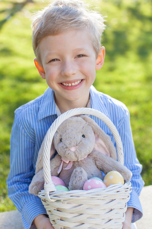 smiling little boy holding easter basket with colorful eggs and bunny at spring time with blooming beautiful tree in the background photo